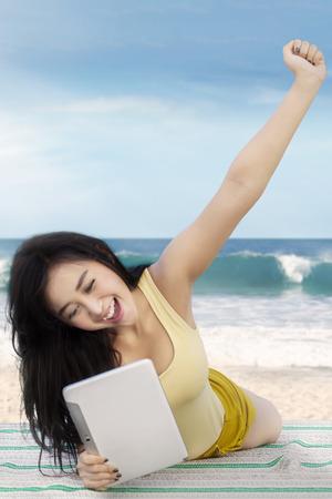 usando computadora: chica joven feliz con el pelo largo, acostado en la playa durante el uso de una tableta digital y levantar la mano Foto de archivo