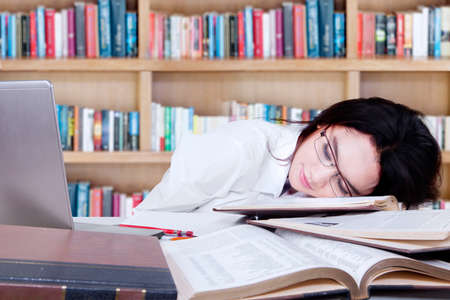 textbooks: Portrait of teenage schoolgirl sleeping above textbooks and laptop on the table in library Stock Photo