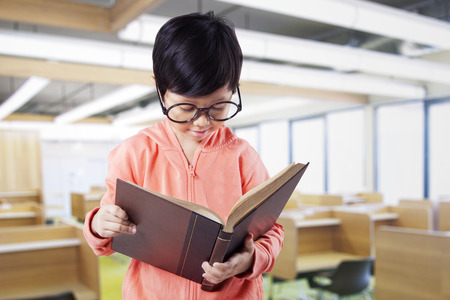 Cute little girl reads a book while wearing glasses and standing in the reading room Stock Photo