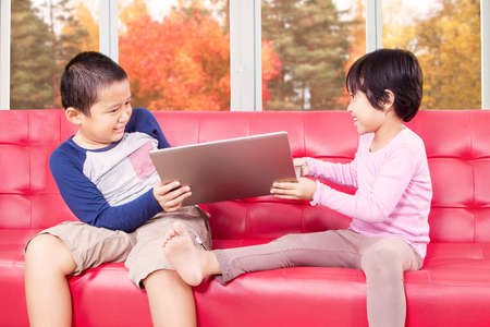 brother sister fight: Portrait of two cute children fighting on the sofa to take laptop computer, shot at home with autumn background on the window Stock Photo
