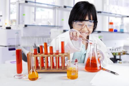 experimento: Foto de una niña que hace la investigación química mientras llevaba gafas y bata en la biblioteca