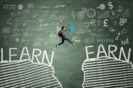 Obrazek żeński szkoła średnia studencki doskakiwanie na chalkboard z tekstem Uczy się i Zarabia