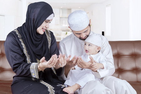 muslim pray: Portrait of two middle eastern parents teaching their son to pray while sitting on the sofa at home