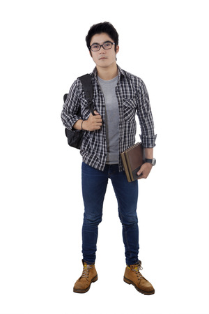 Portrait of male high school student standing in the studio while wearing casual clothes and carrying bag