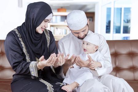 padres e hijos felices: Foto de feliz familia de Oriente Medio y su hijo rezar en casa mientras está sentado en el sofá Foto de archivo