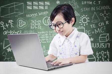 looking at computer: Female elementary school student using laptop while typing on the keyboard and wearing glasses in the classroom