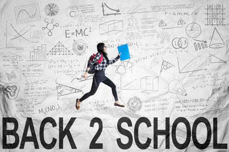 high spirits: Female student back to school and jumping on the crumpled paper background