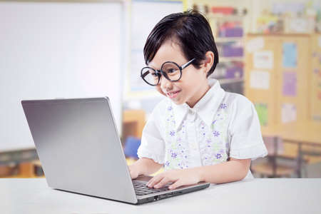 elementary: Portrait of a cute female kid studying in the classroom while using laptop computer on desk Stock Photo