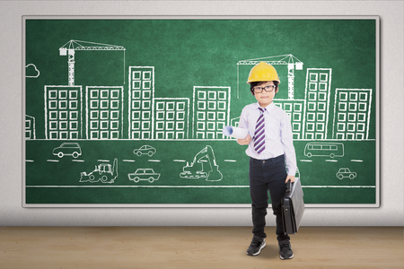 Picture of a little architect carrying blueprint and briefcase with a picture of buildings on the blackboard
