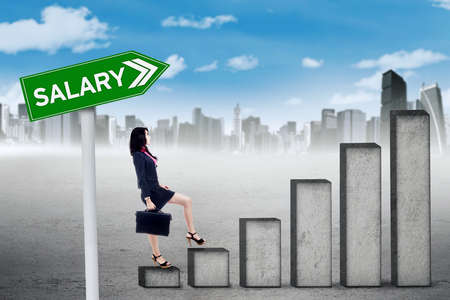 upward graph: Young businesswoman stepping upward on the graph with signpost of salary