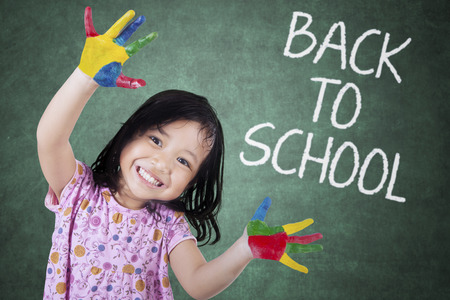 Little girl showing painted hands with back to school text on chalkboard Stock Photo