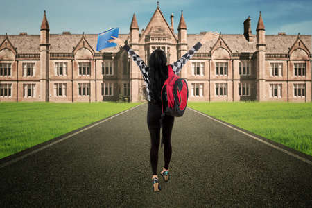 view girl: Female student walk alone to campus rear view Stock Photo