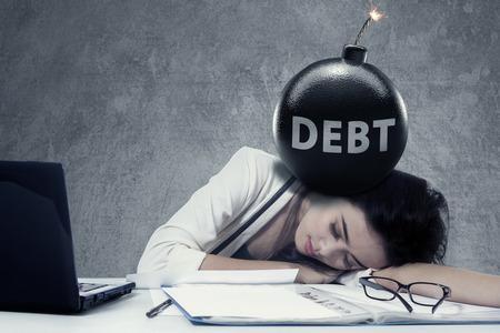 Stressful businesswoman spania na biurko z tekstem długu na bomby na jej głowie