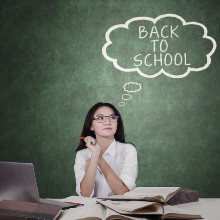 imagines: Female high school student imagines text of Back to School, shot with books and laptop on desk Stock Photo