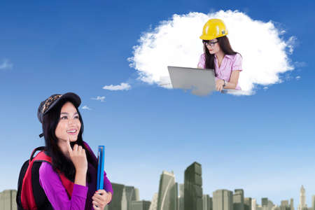 imagines: Female college student imagines work as an architect while looking at speech bubble Stock Photo