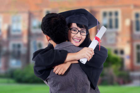 graduate: Female bachelor celebrating her graduation while hugging her boyfriend and wearing a mortarboard