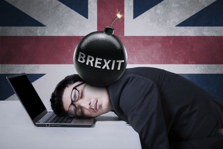 Frustrated businessman sleeping on laptop with text of Brexit on the bomb at his head, shot with UK flag background