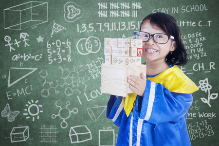 letter blocks: Female primary school student holding letter blocks in the class with scribble on the chalkboard Stock Photo