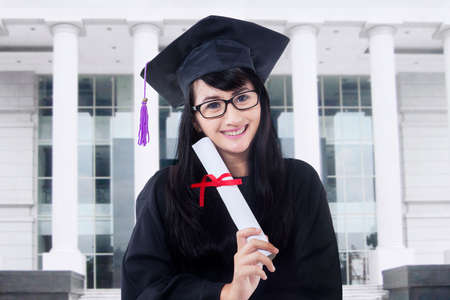 mortarboard: Picture of a female bachelor holding a diploma while wearing a mortarboard in the campus