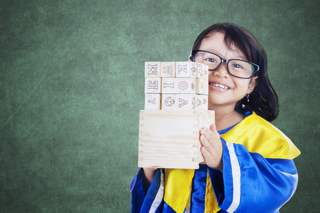 letter blocks: Picture of a little schoolgirl holding letter blocks in the classroom while wearing a graduation gown