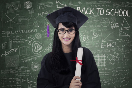 asia people: Picture of a female bachelor standing in the classroom while holding a certificate and wearing graduation cap