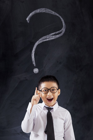 unknowing: Male elementary school student standing in the classroom with question mark on the blackboard Stock Photo