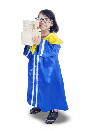 letter blocks: Full length of elementary school student standing in the studio while wearing a graduation gown and letter blocks, isolated on white background Stock Photo