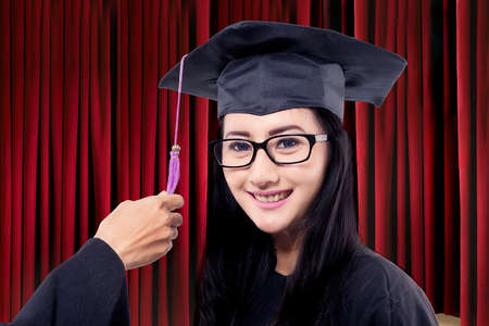 mortarboard: Female bachelor wearing a mortarboard with hand moving the tassel