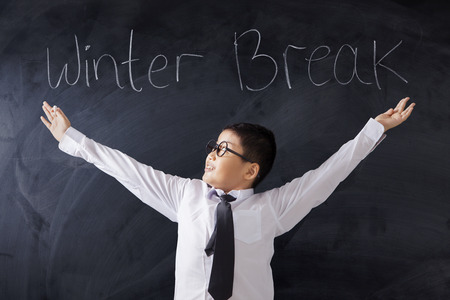 break: Photo of a male primary school student standing in the classroom with text of Winter Break on the blackboard Stock Photo