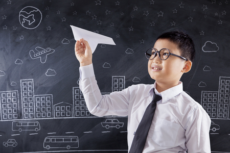 young male: Portrait of a cute schoolboy playing a paper airplane in the classroom