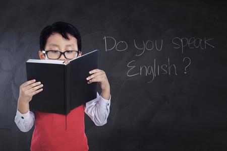 Ragazzino che legge un libro mentre indossa occhiali e uniforme con testo Parli inglese alla lavagna