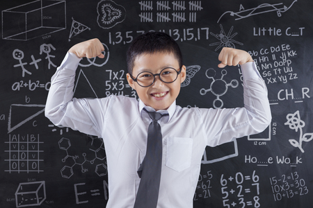 showing: Photo of a strong little boy showing his power in the class while wearing glasses with scribble on the blackboard