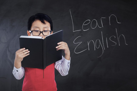 Photo of a male primary school student reading a book with text Learn English on the chalkboard, shot in the class Stock Photo