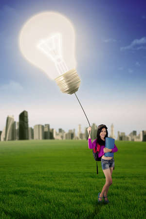 bulb fields: Beautiful female high school student standing on the meadow while holding a bright lightbulb
