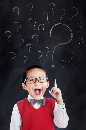 unknowing: Portrait of a little schoolboy wearing glasses and uniform in the class with question marks on the chalkboard Stock Photo