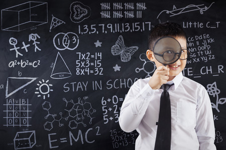 asia children: Image of a schoolboy looking at the camera through magnifier with doodles on the blackboard, shot in the class