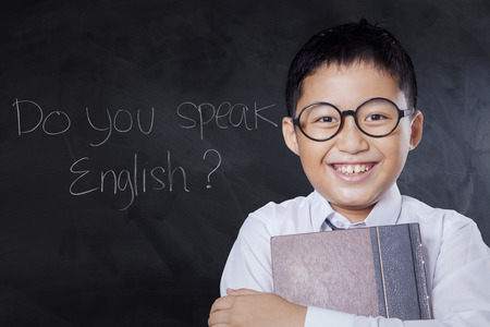 Portrait of a cheerful little boy holding a textbook and smiling in the classroom with text Do You Speak English Stock Photo