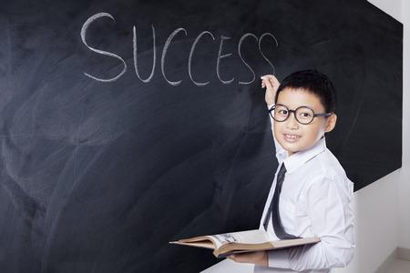 niños estudiando: niño pequeño escribe la palabra éxito en la pizarra mientras sostiene un libro y sonriendo a la cámara, un disparo en la clase