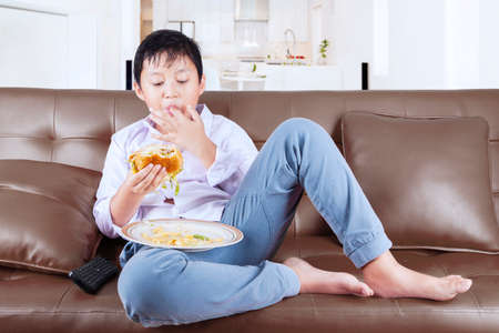 obesity kids: Overweight little boy enjoy cheeseburger while sitting on the couch and suck his finger at home