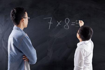 multiplicacion: El niño pequeño escribe la respuesta de la fórmula de multiplicación en la pizarra con su maestro en la clase