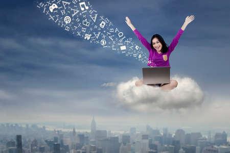 mujeres felices: Retrato de un estudiante femenino alegre usando la computadora portátil mientras está sentado en la nube y enviar el mensaje de
