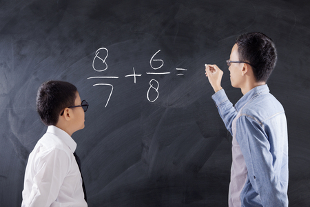 asian teacher: Photo of a young man teaches equations formula on the little boy while writing on the blackboard, shot in the class