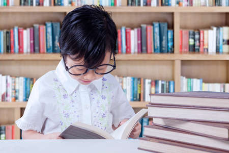 asia children: Photo of adorable female elementary school student reading books on the table in the library