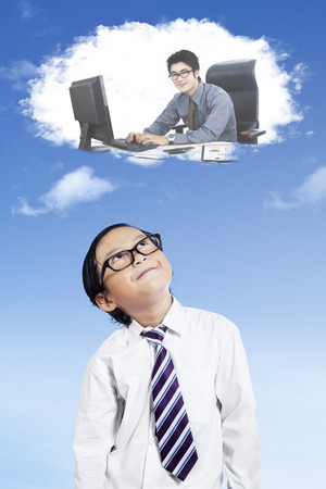 imagines: Cute little boy imagines work as a businessman while looking at speech bubble