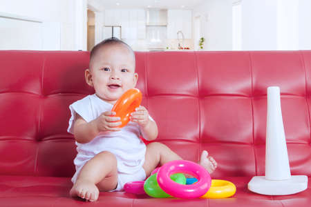 red couch: Portrait of small baby sitting on the red couch and playing a pyramid toy at home