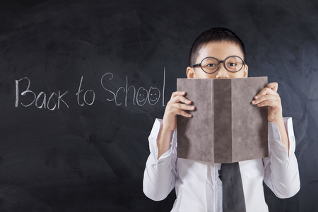 covering: Male elementary school student covering his face using a book with text Back to School on the blackboard Stock Photo