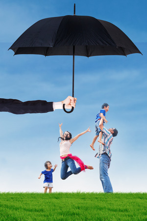 asian lifestyle: Portrait of happy family jumping on the meadow under umbrella. Life and family insurance concept