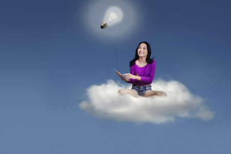 Online Business: Female college student using a digital tablet while sitting on the cloud and looking at a bright lightbulb