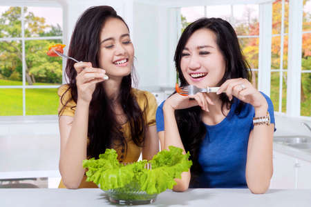 eating salad: Portrait of two Asian girls eating tomato with a bowl of fresh salad on the table  in the kitchen