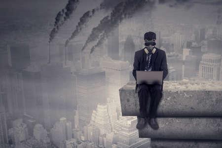 atmosfera: Trabajador de sexo masculino que trabaja en la azotea durante el uso de ordenador portátil y usar una máscara de gas con la contaminación del aire en la ciudad